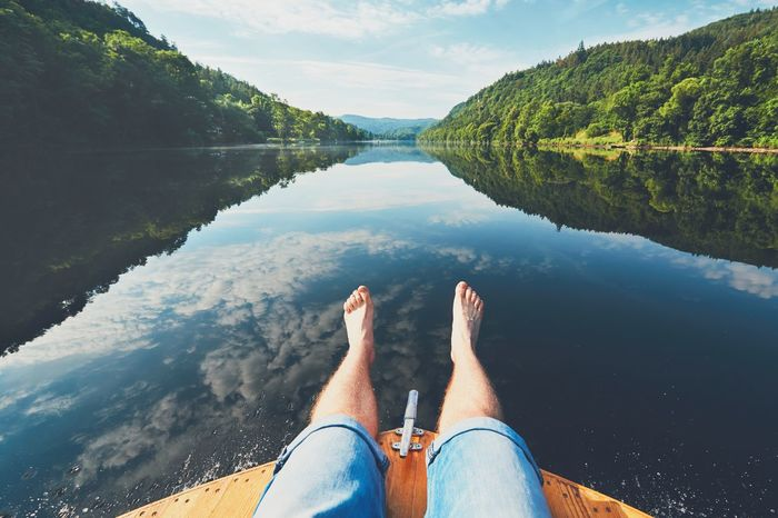 Summer relaxation on the river. The legs of a man sitting on the bow of the boat. Vltava river near Prague, Czech Republic Adventure Boat Floating Floating On Water Foot Human Leg Idyllic Leg Man Nature Outdoors Real People Recreational Pursuit Relaxation Rest River Ship Shorts Summer Summertime Travel Vacations Water Yacht Yachting