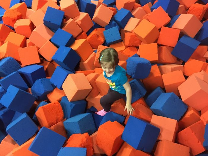 High angle view of girl playing on cube shape sponge