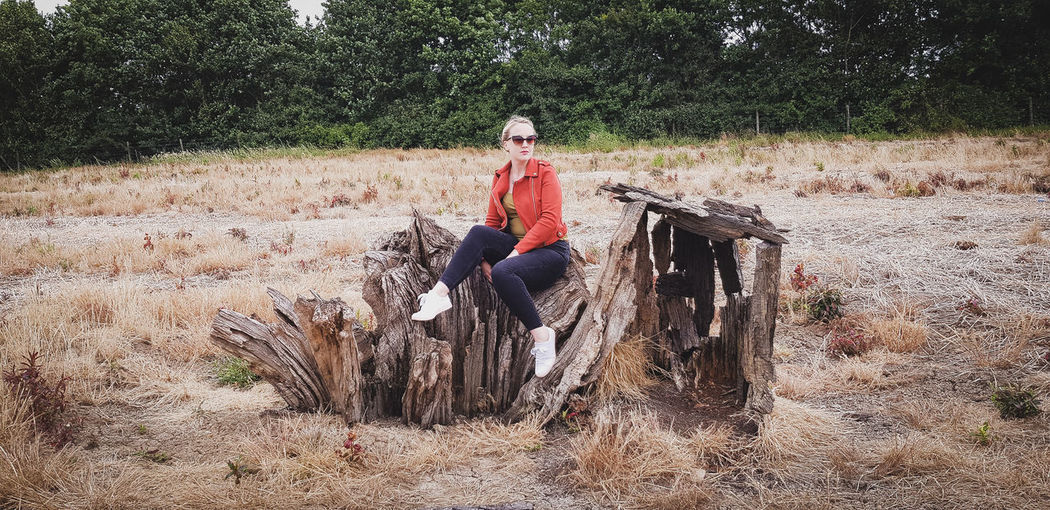 Person sitting on wooden logs on field