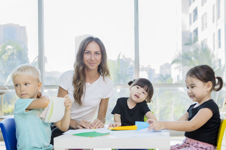 Portrait of mid adult teacher sitting with students in classroom at school