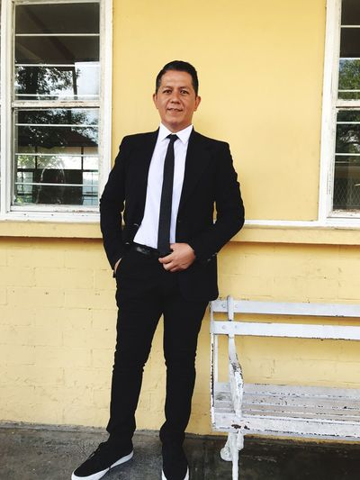 Portrait of man in suit standing against building