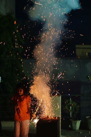 Girl Standing By Firework Display At Night