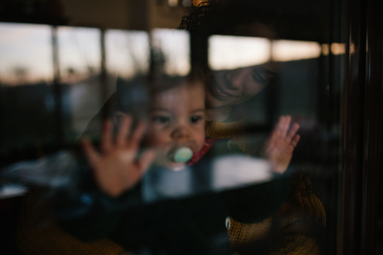 Woman with baby girl seen through glass window