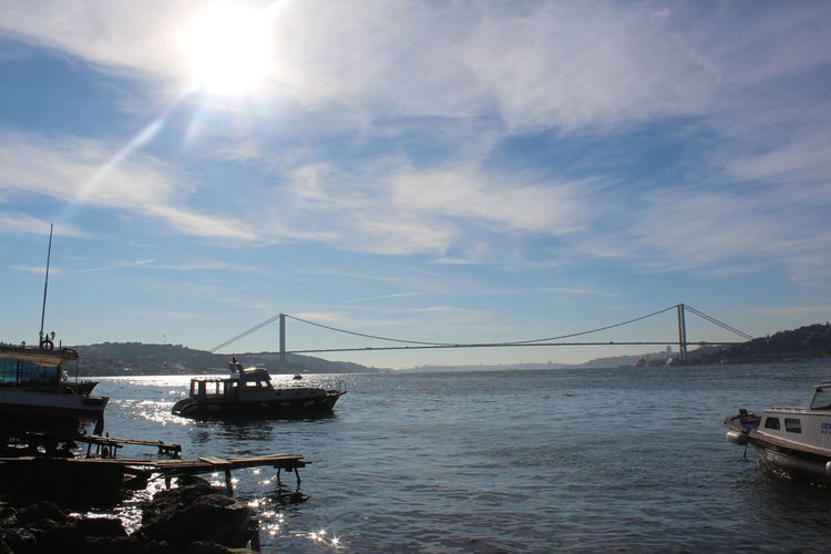 Boats in sea against bosphorus bridge on sunny day
