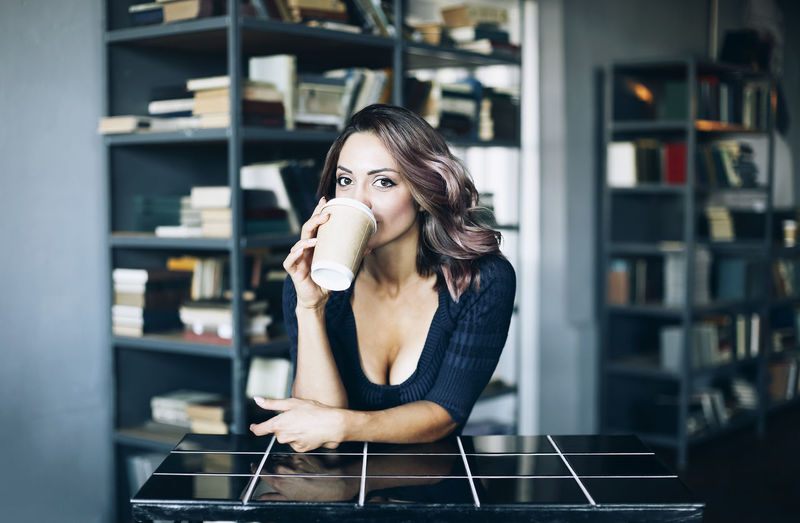 Portrait of young woman drinking coffee indoors