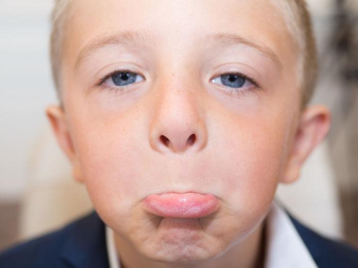 Close-up portrait of cute boy making face