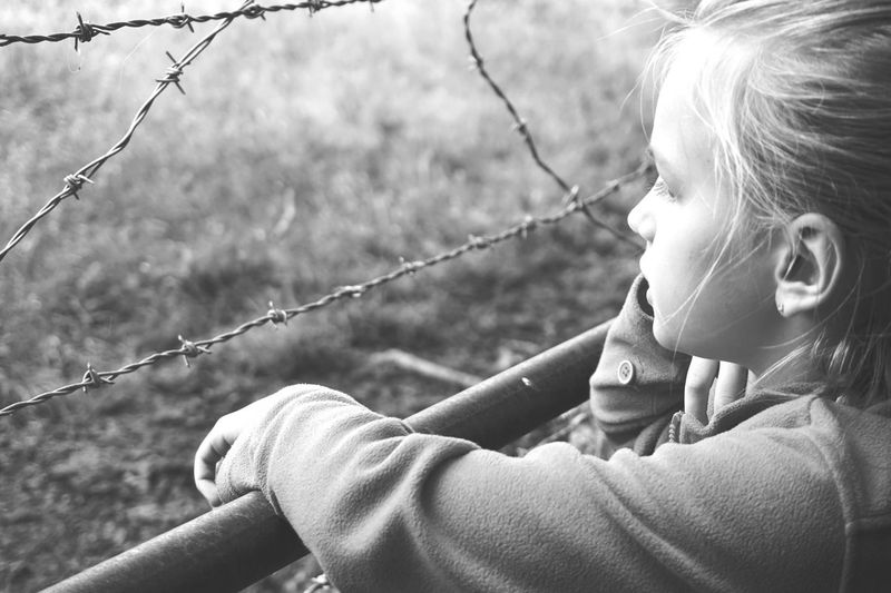 Close-Up Of Thoughtful Girl By Barbed Wire Fence