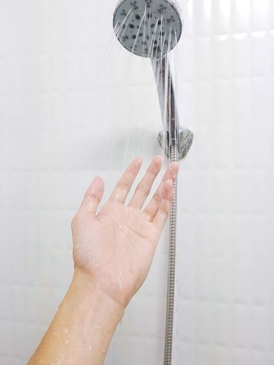 Cropped hand of woman under shower in bathroom