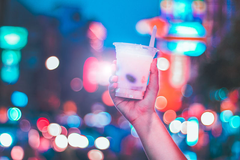 Cropped hand holding drink against illuminated background