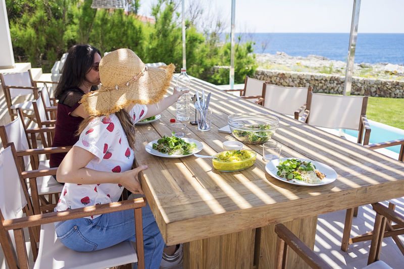 Side view of two woman sitting while having a healthy dinner in front of the sea Table Women Seat Food And Drink Chair Food Lifestyles Real People Healthy Eating Day Wellbeing Water Leisure Activity Nature Wood - Material Sitting Adult Two People Relaxation Outdoors