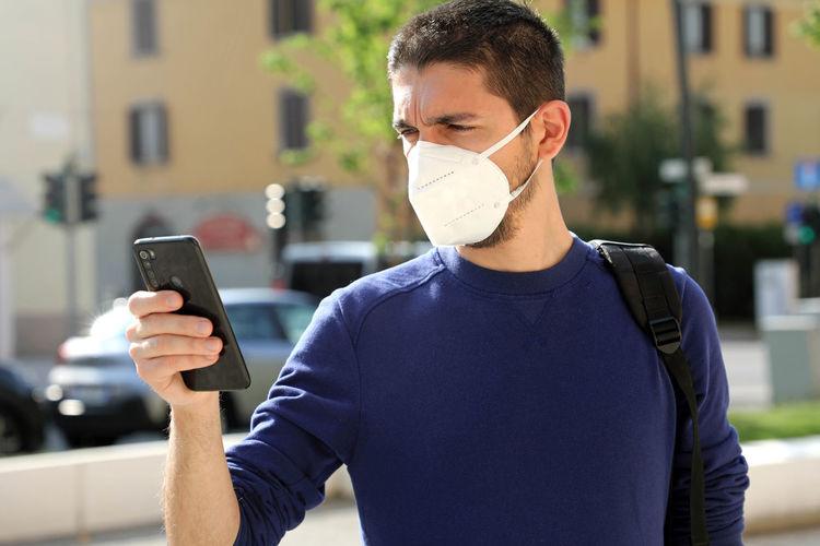 Man wearing man while using phone in city