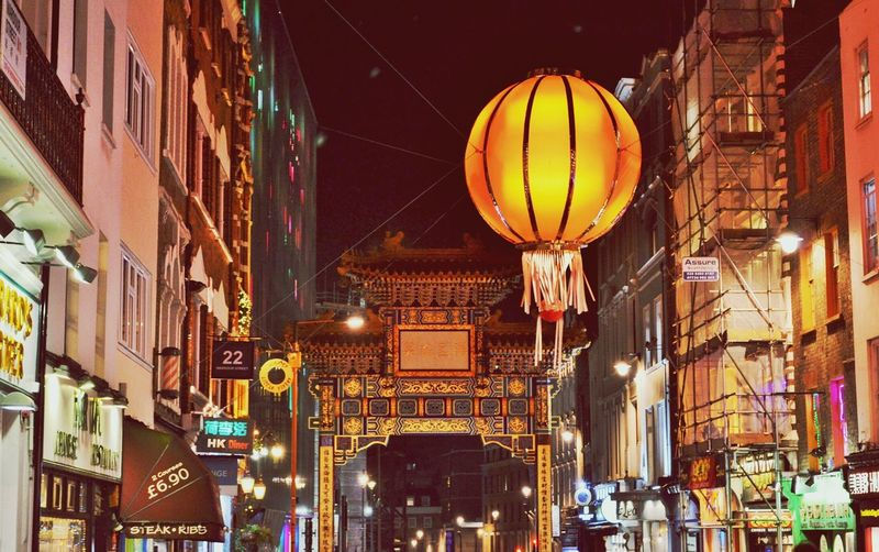 Low Angle View Of Illuminated Lantern Amidst Buildings In Chinatown At Night