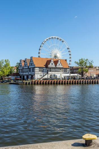 Ferris wheel by river against clear blue sky