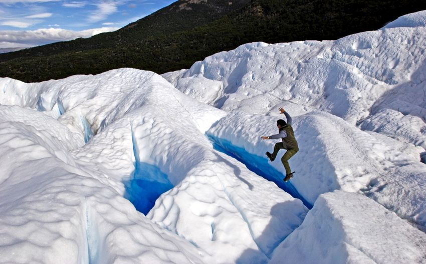 High angle view of man jumping on glacier