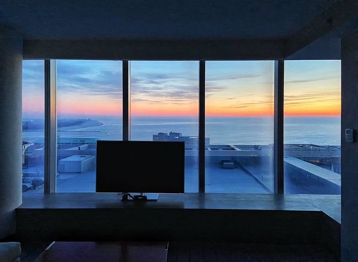 Scenic view of sea against sky during sunset seen through window