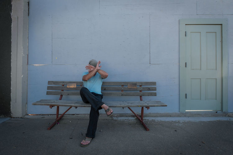 No photo, please. mature man sitting on bench against light blue wall hiding his face