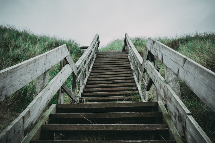 Wooden staircase on field against sky