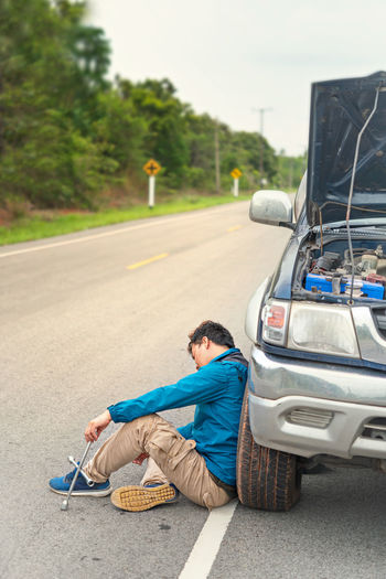 Man sitting by broken down car on road
