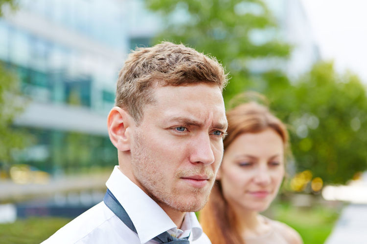 Close-up of young man looking away while standing by woman