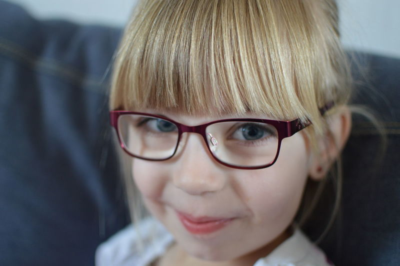 Close-up portrait of cute smiling girl wearing eyeglasses
