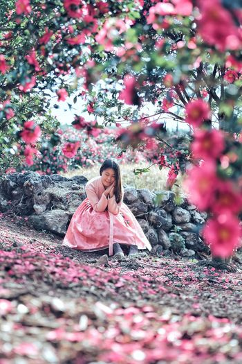 Woman sitting on rocks wearing a pink dress with pink flowering plant in the foreground