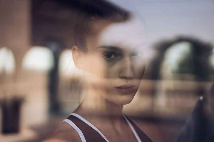 Close-up portrait of young woman looking through the window