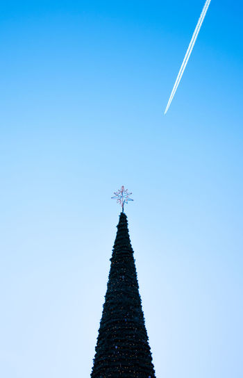 Christmas tree. Christmas Jet Plane New Year Around The World New Year Plane Blue Christmas Decoration Christmas Tree Clear Sky Contrasting Textures Day Events Low Angle View No People Outdoors Plane Flying Sky Smoke Travel Vapor Trail White Trail