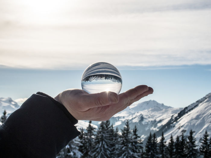 Close-up of hand holding transparent ball against snowed plants