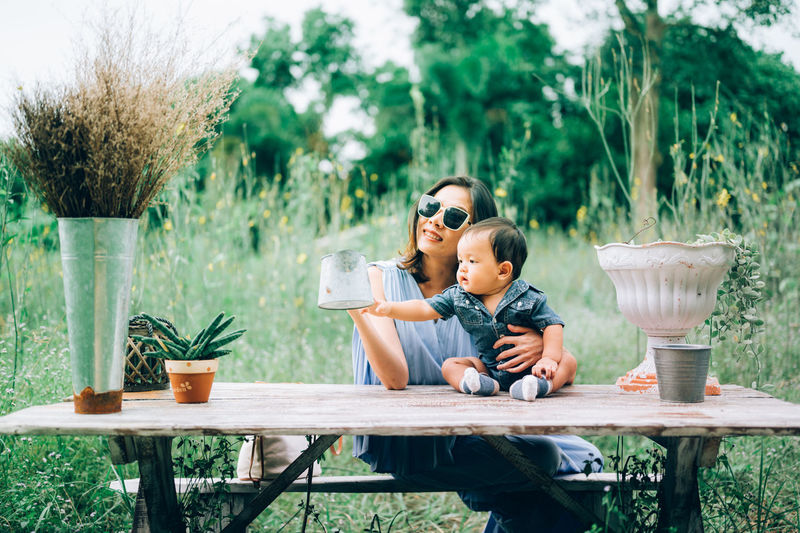 Mother sitting with son on bench in field