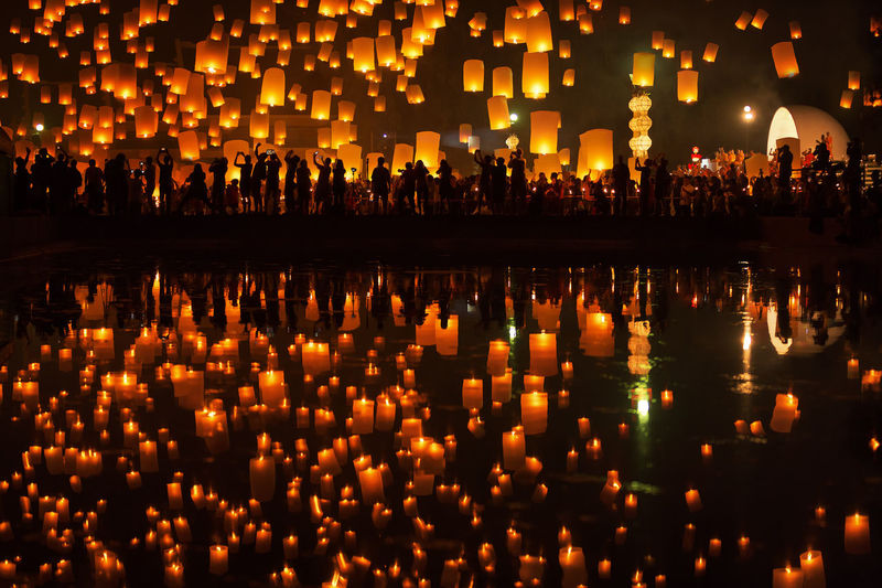 Illuminated lanterns reflecting on pond in city at night during yi peng