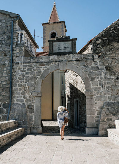 Rear view of young woman standing in front of gates of old town. summer, tourism, travel.