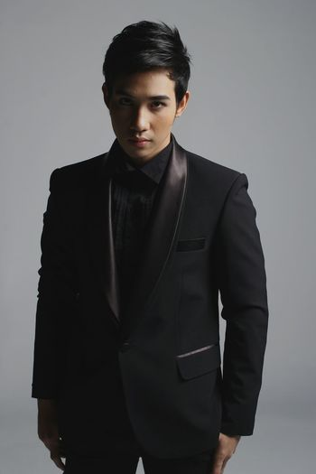 Portrait of male model in suit standing against gray background
