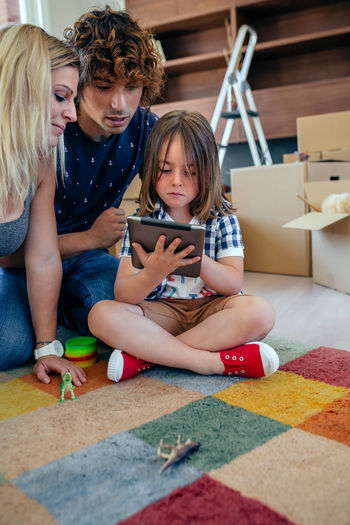 Parents supervising their little son playing the tablet sitting on the floor of the living room Family Fun Happiness Happy Moving Tablet Unpacking Woman Apartment Boxes Boy Cardboard Home Interior House Indoors  Lifestyles Living Room Mammal New Home Packing Placing Real People Relocating Three People Vertical