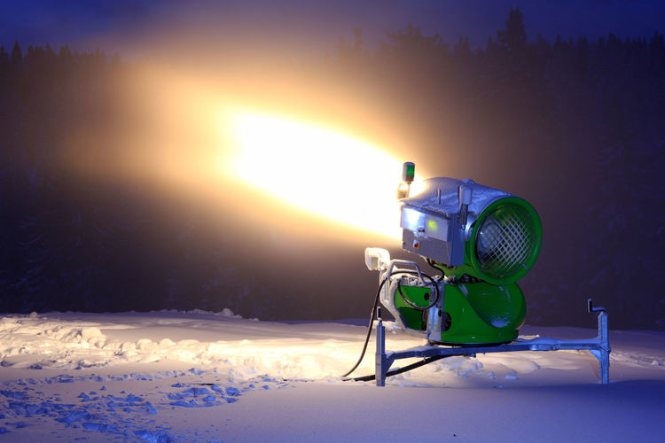 Snow making machine making snow in the night Beauty In Nature Camera - Photographic Equipment Cold Temperature Field Freezing Illuminated Nature Night No People Nobody Orange Color Outdoors Sky Snow Snow Cannon Snow Machine Snow Making Machine Technology Winter