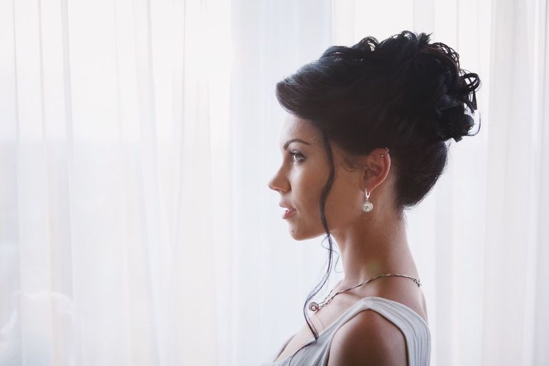 Side View Of Beautiful Woman Standing Against Curtain