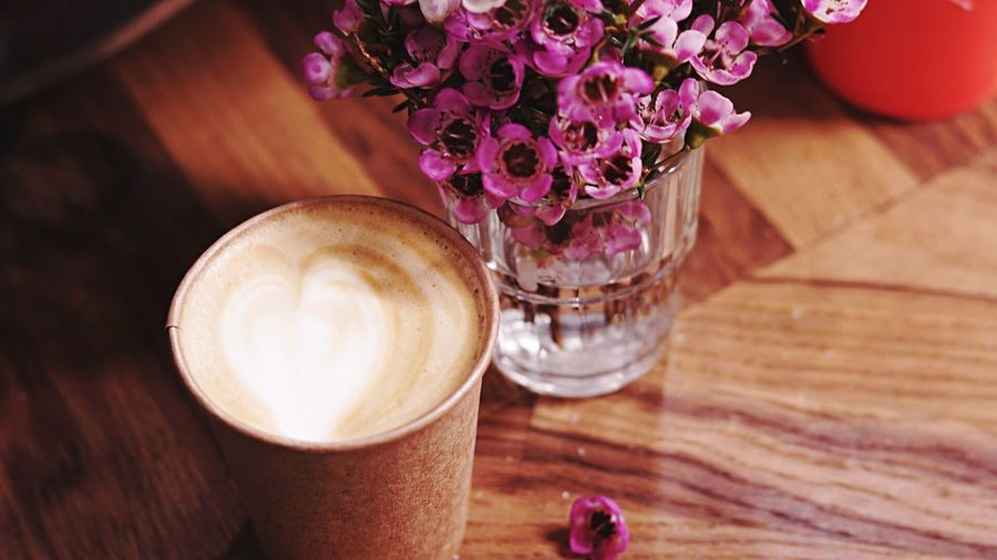 High Angle View Of Coffee By Flowers On Table