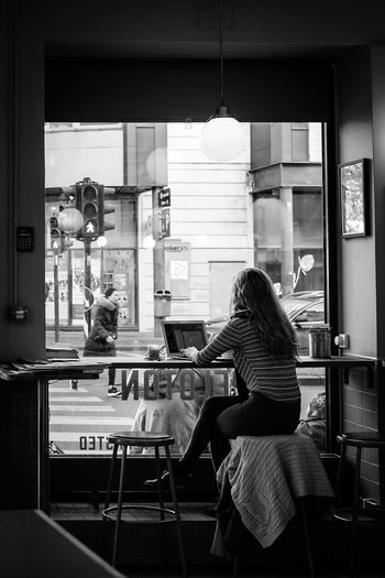 World going by Coffee Woman Working Street Photography Streetphotography Window Computer Laptop Real People Women Lifestyles Indoors  Sitting Seat Adult People Leisure Activity Rear View Cafe Chair