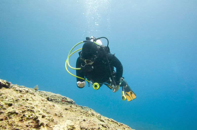Scuba Diver Exploring Coral Reef Underwater Scuba Diving Adventure Exploration Sea Wetsuit Marine Life Mediterranean  Activity Flippers Water Aquatic Sport UnderSea Nature Sea Life Extreme Sports underwater photography Woman Blue Reef Diving Equipment One Person Scuba Mask Diving Flipper Underwater Diving