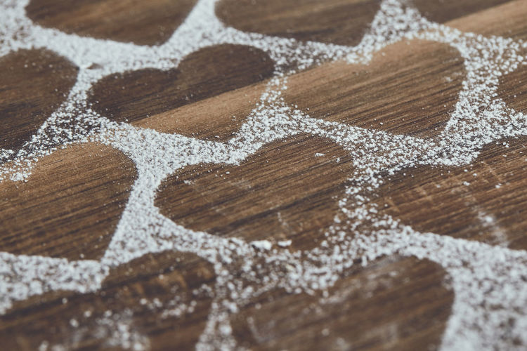 High angle view of heart shapes amidst powdered sugar on table