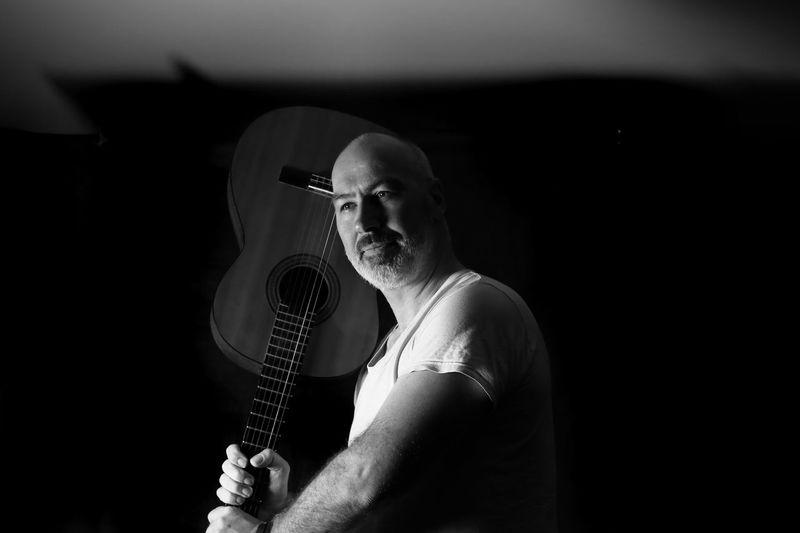 Bald man holding guitar against black background