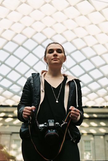Low angle portrait of woman holding camera against skylight