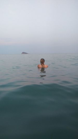 Person swimming in sea against sky