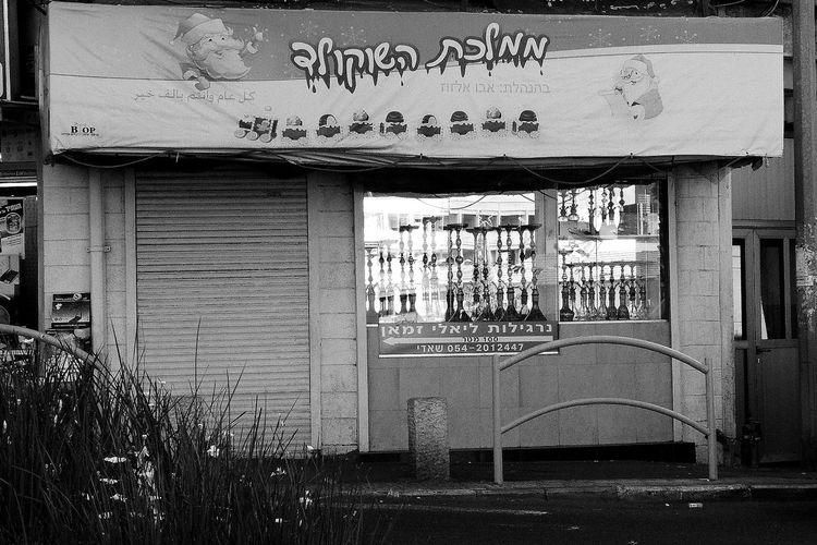 Haifa, Israel An arabic shop selling narghilè with a sign on Christmas Time Un negozio arabo vende narghilé con un'insegna con Babbo Natale Babbo Natale Christmas Santa Klaus Selling In Arabian Shop Wadi Nisnas Arabic People In Israel Israele Medioriente Musulmani Narghile Natale  Outdoors Palestinesi People Popolazione Shop