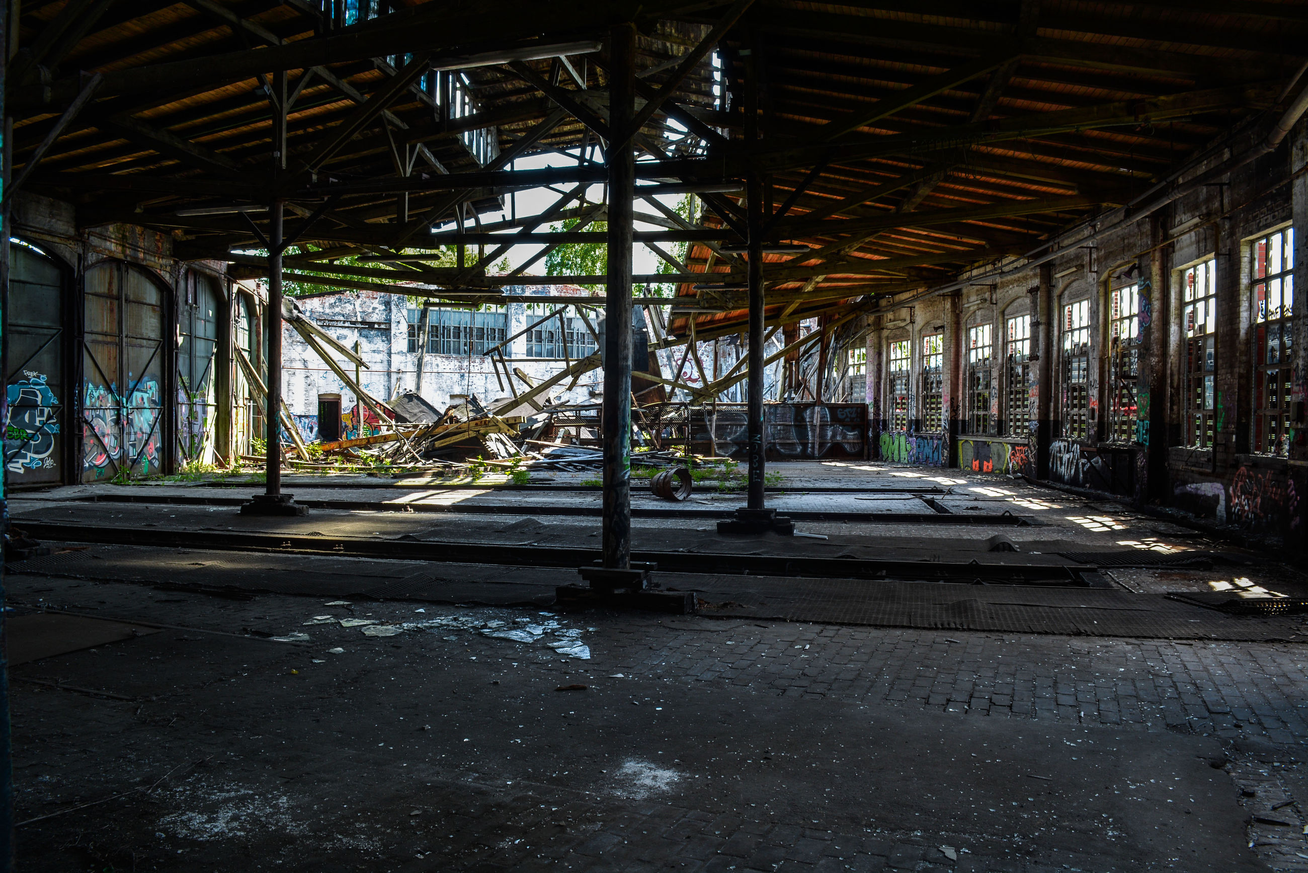 built structure, architecture, indoors, abandoned, obsolete, graffiti, metal, damaged, architectural column, run-down, interior, empty, sunlight, day, deterioration, old, ceiling, window, transportation, the way forward
