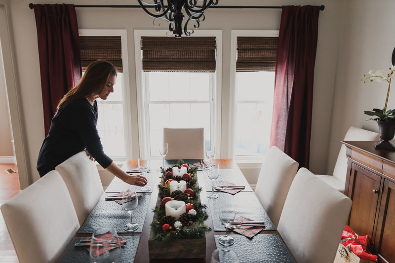 Side view of woman sitting on table at home
