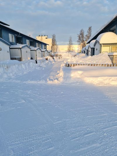 Snow covered houses on field by building against sky