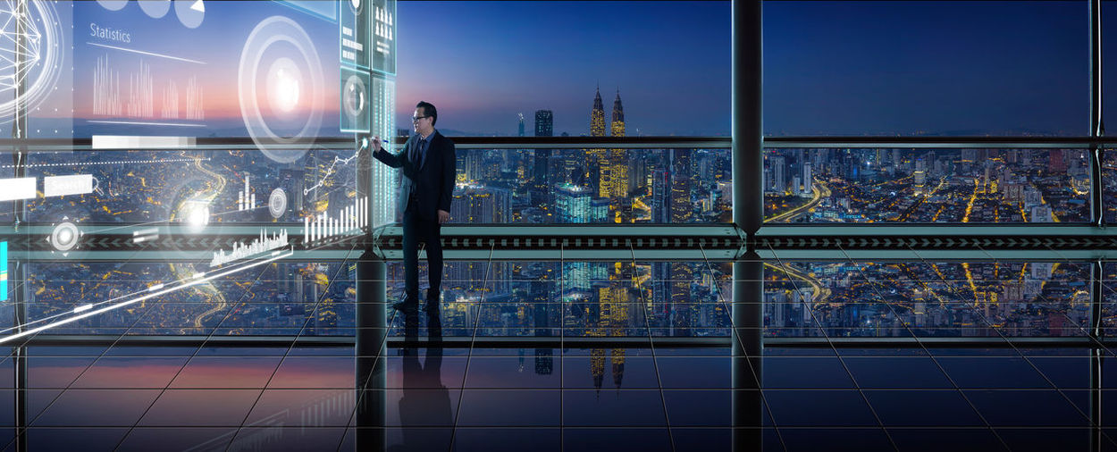 Digital Composite Image Of Businessman With Icons Working In Office At Night