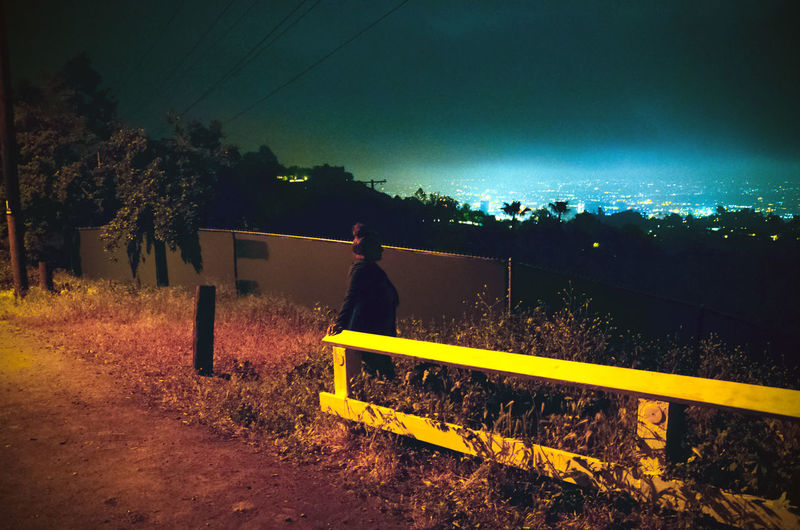 Adult Alone In The City  Fence Hollywood Bowl Scenic Overlook Leisure Activity Neon Color Night One Person Sky Tree View From Above