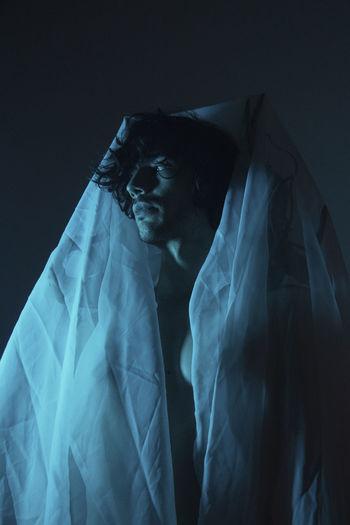 Man wearing mask against black background