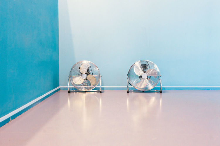 Air blower fans on the ground in front of blue wall Air Blower Blue Fan Heat Indoors  No People Pair Summer Two Wall